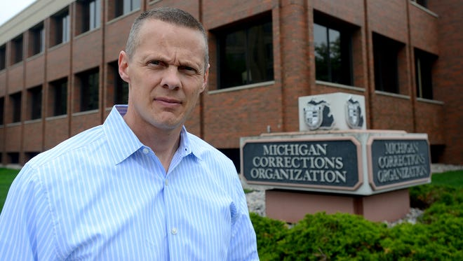 Corrections officers are largely supportive of a system that digitally logs the officers' rounds and soon will be installed in all Michigan prisons.  Andy Potter, the new VP and chief of staff for the Michigan Corrections Organization, stands outside the union's office in Lansing  May 6, 2015.