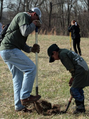 Rajv Menon of Independence, and his son Ashwin, work on plating trees in 2010, during the Reforest Northern Kentucky event in Union.