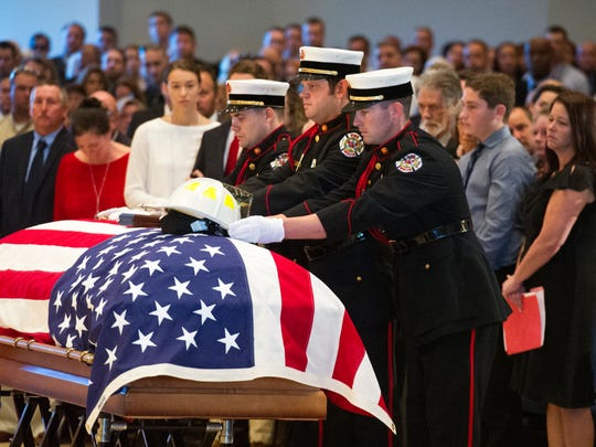 """The guy was a character. We shared a lot of laughs together. But he was also the guy who would give everything to help another person. It was an honor for me to place that helmet,"" said Indian River County firefighter Christopher Barcus (center right) who places Indian River County Fire Rescue Battalion Chief David Dangerfield's helmet on his casket during a celebration of life memorial service Oct. 22, 2016, at Community Church of Vero Beach."