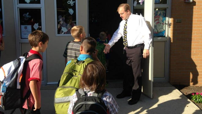 Principal Eric Renfors greeting students at Kennedy School.