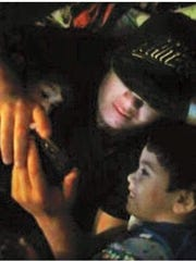 Nathaniel Gutierrez looks at his phone with his two sons, Lincoln (far left) and Nathan.