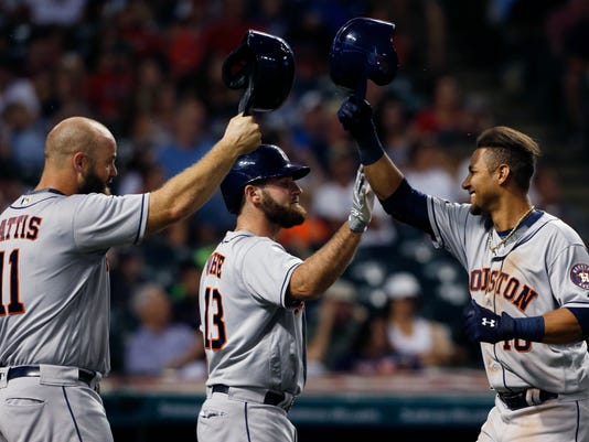 Houston Astros' Yulieski Gurriel (10) gets congratulations from Tyler White (13) and Evan Gattis (11) after hitting a two-run home run off Cleveland Indians relief pitcher Andrew Miller during the eighth inning of a baseball game Wednesday, Sept. 7, 2016, in Cleveland. (AP Photo/Ron Schwane)