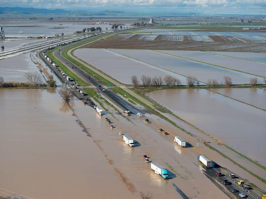 In this view looking north, flood water crosses over Interstate 5 at Williams, backing up traffic in both north and southbound lanes for hours on Saturday. Northern California and the San Francisco Bay Area were facing a weekend return of heavy rain and winds that lashed them earlier in the week before the storm moves out.