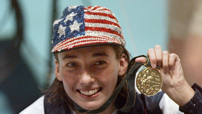 In this July 26, 1996 file photo, Olympic gold medalist Amy Van Dyken holds her medal after winning the women's 50 meter freestyle at the 1996 Summer Olympic Games in Atlanta.