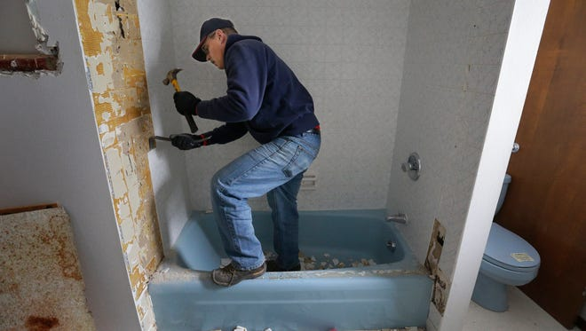 VFV member Marc Wildeman of Black Creek works as a volunteer for Housing Partnership of the Fox Cities removing shower tiles in a duplex for transitional housing for veterans with families who stand at risk for homelessness Tuesday in Appleton. The home is at 719 W. Packard St.
