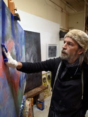 Jimmy Abegg paints in his studio Tuesday, Feb. 16,
