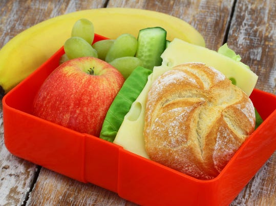 Lunch box containing cheese sandwich, apple, grapes and banana