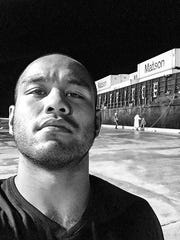 Mixed martial arts star Frank Camacho waits for a container of donated supplies to to be unloaded from a ship at a port on Saipan provide aid following Super Typhoon Soudelor.