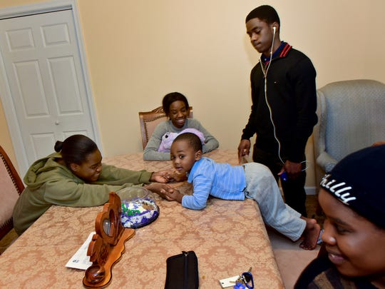 From left, Lewis children Adhassa, Milca, Isaiah, Adlai and Ananie hang out in the kitchen of their Habitat for Humanity home on Tuesday, just days before they will celebrate their first Christmas there.