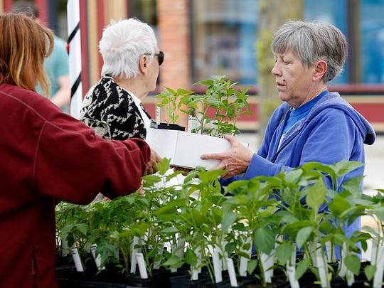 Susan Horvath of Fond du Lac buys some vegetables Saturday May 13, 2017, during the opening weekend of the Downtown Fond du Lac Farmers Market. Doug Raflik/USA TODAY NETWORK-Wisconsin