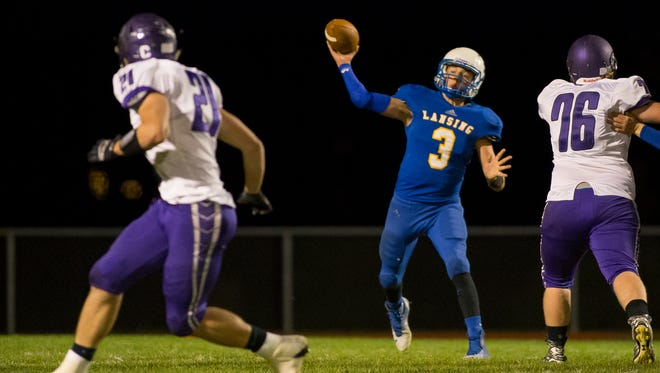 Lansing quarterback Mason Boothe throws a pass as Dryden's Stu Stahlman (21) looks for the ball during their game on Oct. 2 at Lansing. The Bobcats will forfeit their home game Friday night against two-time defending state champion Chenango Forks due to a lack of healthy players, according to Lansing AD Adam Heck and coach John Winslow.
