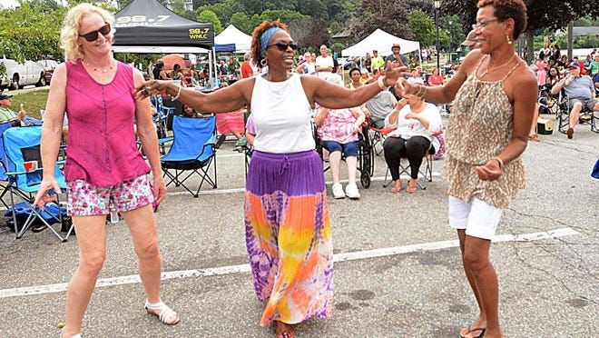 Amy Helie of Baltic, left, Della Evans of Norwich and Rose Marie Josiah of Waterford dance to the reggae music of Hope Road a year ago during the weekly free Rock the Docks at Howard T. Brown Memorial Park in downtown Norwich. This summer, the event has been moved to Dodd Stadium.