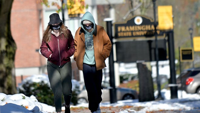 A  pair of students  make their way across campus  at Framingham State University on Saturday, Oct. 31.