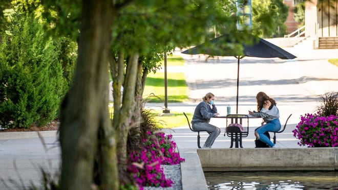"""Two students sit near the Zumberge Pond during the first day of classes at Grand Valley State University on August 31, 2020. GVSU students are being told to practice """"enhanced safety measures,"""" including largely staying in their rooms in order to limit exposure to COVID-19 and the possibility of taking the virus back to their home communities."""