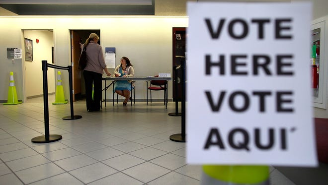 An election official answers a question for a voter on Nov. 6, 2012, in Mansfield, Texas.
