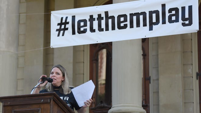 Jayme McElvany, mother of Milan quarterback Cole McElvany, speaks during a rally for high school football in Michigan at the state capital Friday.