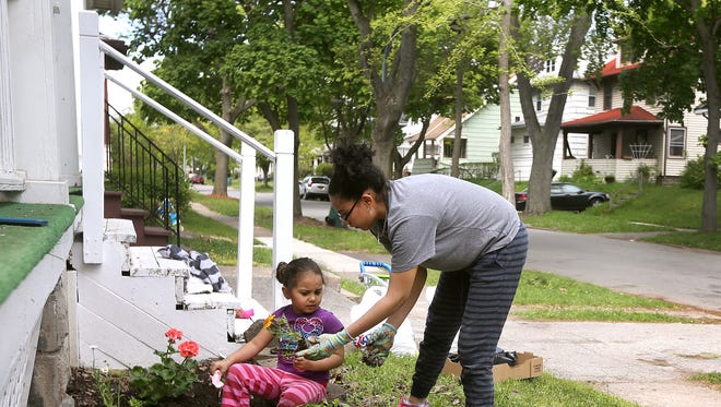 Monique Santiago and her daughter Rosaley Villagas, 3, plant flowers outside their home on Hazelwood Terrace in the Beechwood Neighborhood. Beechwood is one of the first neighborhoods the anti-poverty initiative hopes to address.