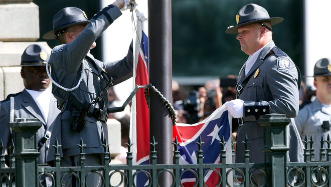 An honor guard from the South Carolina Highway patrol lowers the Confederate battle flag as it is removed Friday from the Capitol grounds in Columbia, S.C. Legions of people clapped, cheered and cried as South Carolina lowered the Confederate battle flag. But as the euphoria of the moment faded, questions over what exactly that accomplished for race relations in the United States, other than the elimination of a painful symbol of the past, began to arise.
