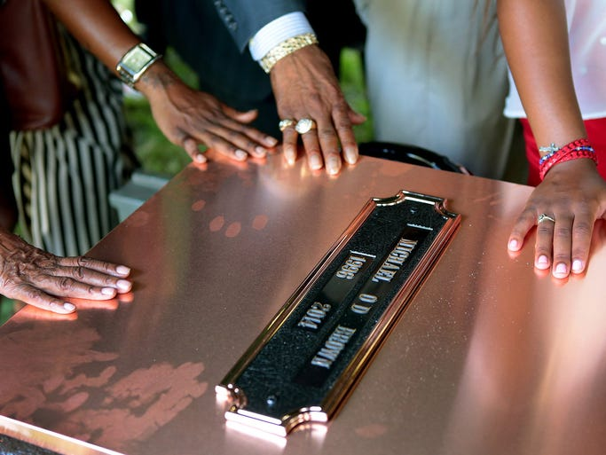 FILE - In this Monday, Aug. 25, 2014, file photo, family members touch the copper top of the vault containing the casket of Michael Brown during his funeral in Normandy, Mo. Hundreds of people gathered to say goodbye to Brown, who was shot and killed by a Ferguson, Mo., police officer on Aug. 9. (AP Photo/St. Louis Post Dispatch, Robert Cohen, Pool) ORG XMIT: MOSTP603