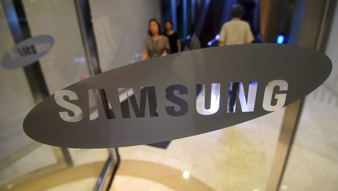 A woman walks past the logo of Samsung at the company's showroom in Seoul on July 7, 2017. Samsung Electronics expects profits to soar 72 percent in the second quarter to a record high, it said on July 7, as it moves on from a recall debacle thanks to rising memory chip prices and increased demand for smartphones. / AFP PHOTO / JUNG Yeon-Je        (Photo credit should read JUNG YEON-JE/AFP/Getty Images)