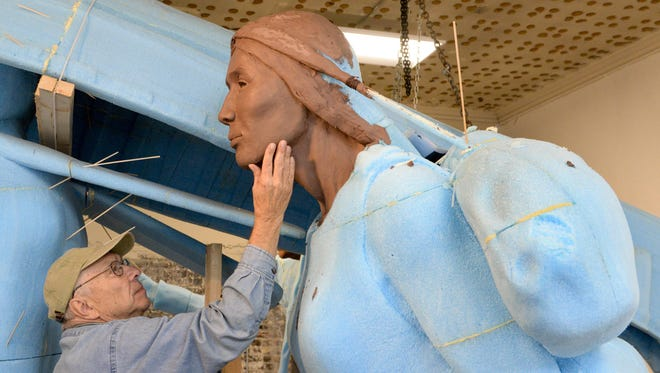 Artist R.T. 'Skip' Wallen, a native of Manitowoc, works on the facial detail of one of the three American Indian figures of the Spirit of the Rivers monument at the studio in downtown Manitowoc.