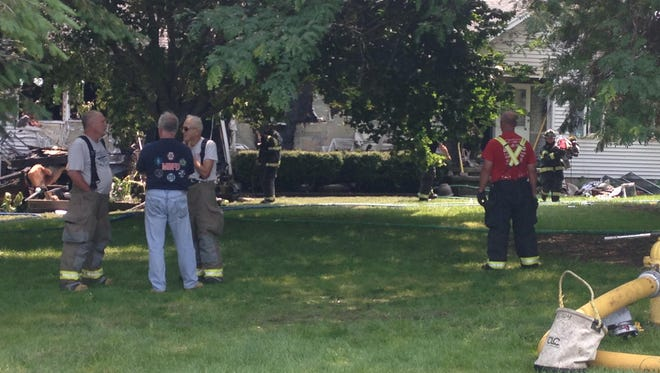 Firefighters work to clear the debris from a Penfield home after fighting a fire there Sunday morning.