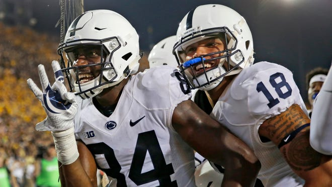Penn State wide receiver Juwan Johnson, left, is congratulated by teammate Jonathan Holland after catching a touchdown pass as time expired to defeat Iowa in an NCAA college football game Saturday, Sept. 23, 2017, in Iowa City, Iowa.