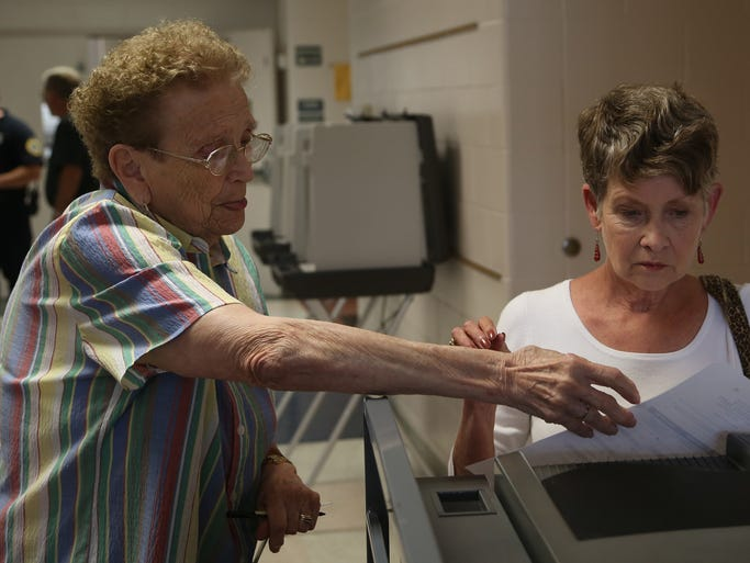 Linda Garrett gets help from election worker Jeri Leo while entering her ballot during primary elections at River Woods School on SE 22nd St. Tuesday, June 3, 2014.
