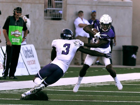 Abilene Christian University wide receiver Justin Miller tries to elude Stephen F. Austin University safety Lawrence Ghansah during Saturday's game at Wildcat Stadium Sept. 23, 2017. ACU lost, 10-20.