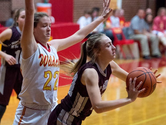 Mount Vernon's Brooke Jackson (20) makes a pass as she is defended by Mater Dei's Jossie Hudson (22) at Mater Dei High School in Evansville, Ind., on Tuesday, Dec. 5, 2017. Mater Dei defeated Mount Vernon 63-56 in overtime.