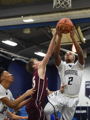 Poughkeepsie's Akili Hill attempts a layup while New Paltz's Matt Kanan attempts to block him during Tuesday's game at Poughkeepsie High School.