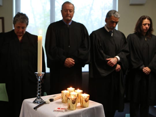 Judges observe a moment of silence after lighting candles