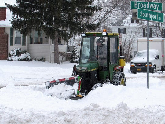 Snow gets removed Wednesday near the intersection of