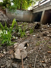 A single boot rests among debris in Mill Creek along Main Street near County Center on Thursday, April 30, 2015.