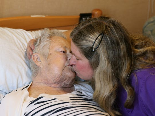 Kathy Ziegler shares tender moment with her mother, Phyllis Purple, after members of the Threshold Choir visited Phyllis to sing at her bedside at Aaron Manor.