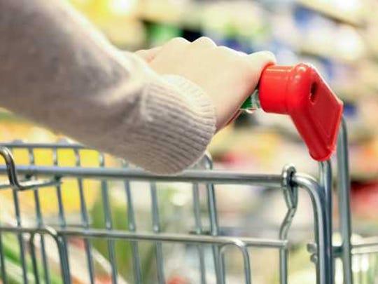 Hands pushing shopping cart down an aisle.