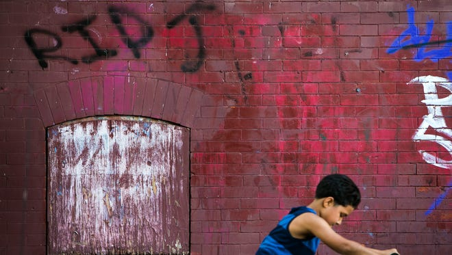 A young boy rides by RIP graffiti on the wall along W. Third and North Broom streets in Wilmington, near where 16-year-old Jordan Ellerbe was gunned down on a front porch in January 2015.