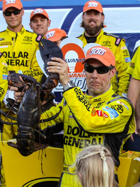 Matt Kenseth holds a lobster in Victory Lane after winning the NASCAR Sprint Cup series auto race at New Hampshire Motor Speedway in Loudon, N.H., Sunday, Sept. 27, 2015, (AP Photo/Cheryl Senter)