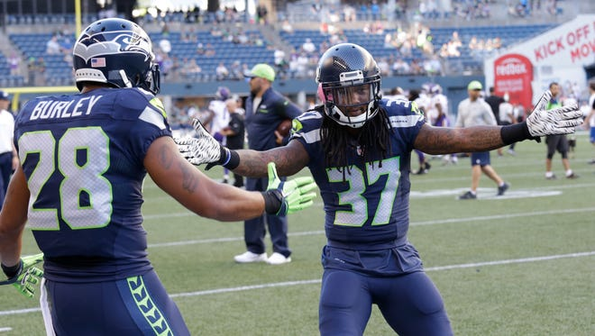 Seattle Seahawks cornerback Trovon Reed greets defensive back Marcus Burley (28) before a preseason NFL football game against the Minnesota Vikings, Thursday, Aug. 18, 2016, in Seattle.