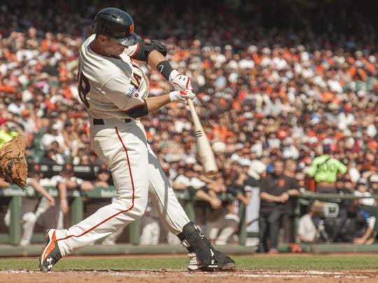 Oct 4, 2015; San Francisco, CA, USA; San Francisco Giants catcher Buster Posey (28) hits an RBI single against the Colorado Rockies during the first inning at AT&T Park. Mandatory Credit: Ed Szczepanski-USA TODAY Sports
