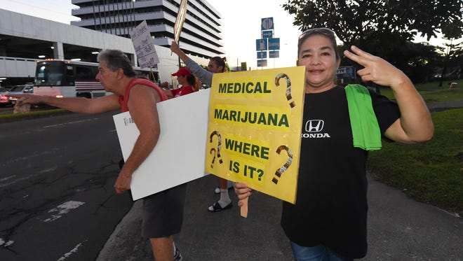 Supporters of the medicinal cannabis program hold a wave at the ITC intersection in Tamuning on Nov. 17, 2017.