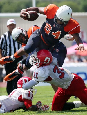 Blackman running back Charlie Davidson (24) tries to leap over Oakland's Josh Smith (31) on Sunday at Blackman.