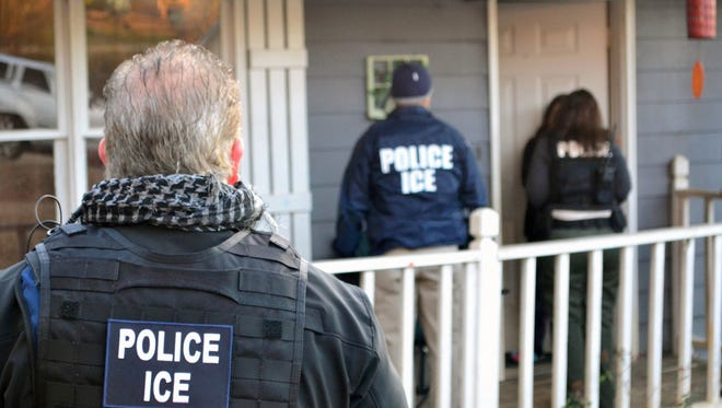 In this Feb. 9, 2017, photo provided by U.S. Immigration and Customs Enforcement, ICE agents visit a home in Atlanta during a targeted enforcement operation aimed at immigration fugitives, re-entrants and at-large criminals living in the U.S. illegally.