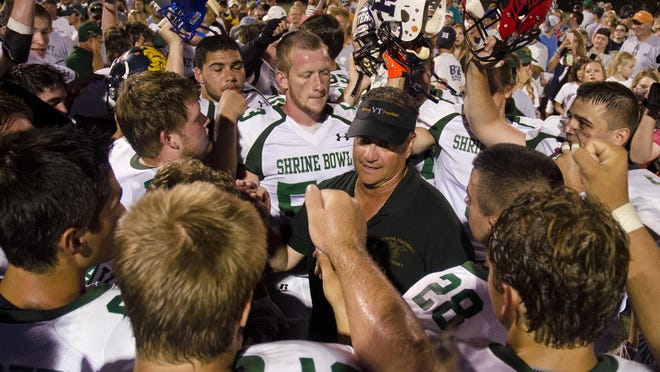 Vermont coach Brian Grady, center, huddles with his team after their historic 50-2 win over New Hampshire in the 63rd annual Shrine Maple Sugar Bowl at Castleton University in August.