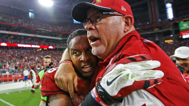 Cardinals head coach Bruce Arians hugs defensive back Rashad Johnson after he broke up a pass in the end zone to secure a 24-20 win against the Philadelphia Eagles on Sunday.
