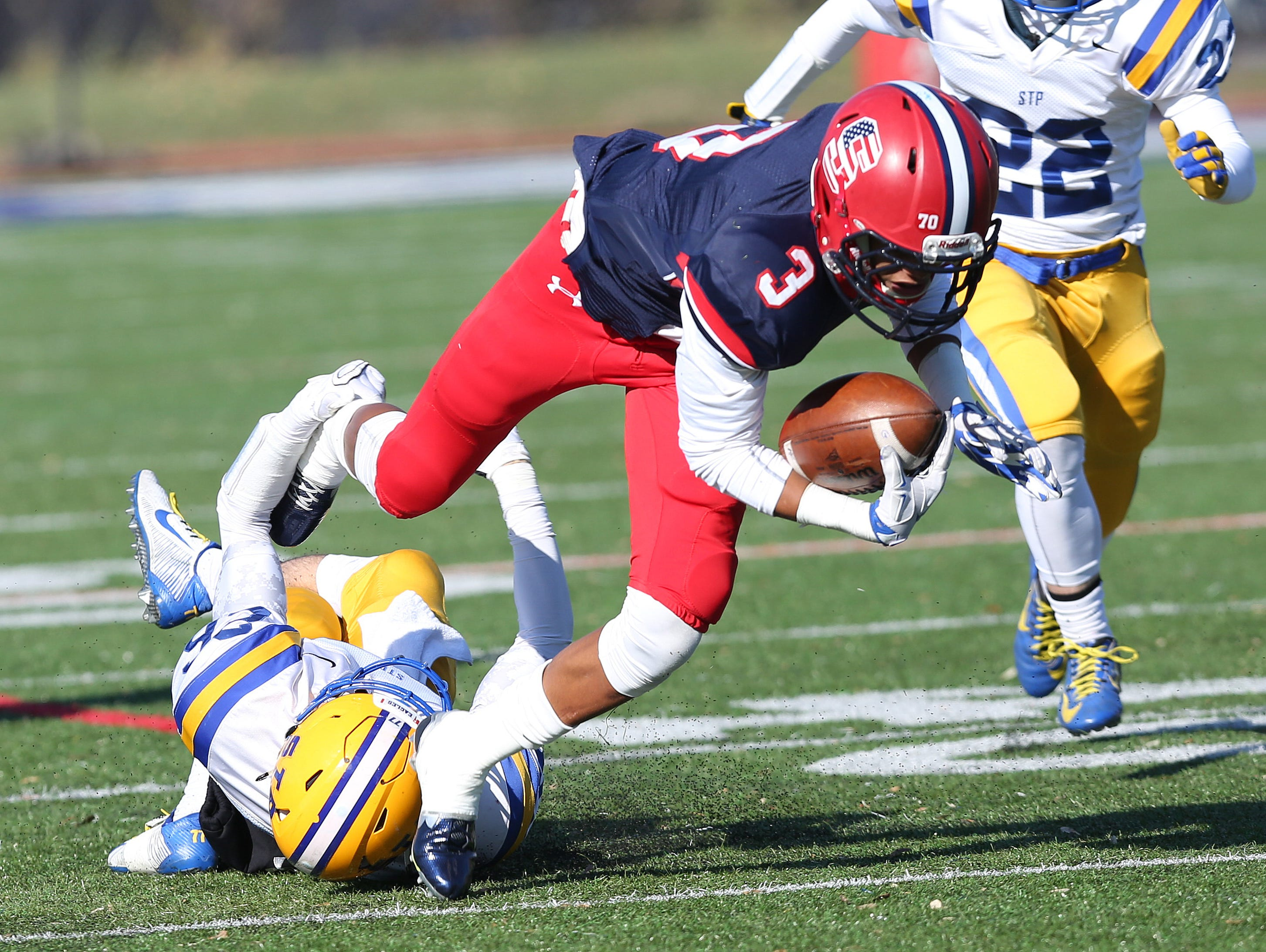 Stepinac's Jesse Brown (3) tries to break away from Saint Peter's Chris Fillippides (26) on a first quarter run during the NYCHSFL semifinals at Archbishop Stepinac High School in White Plains Nov 15, 2015. Stepinac won the game 49-7.