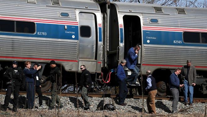 Passengers watch as emergency personnel operate work at the scene of a train crash involving a garbage truck in Crozet, Va., on  Jan. 31, 2018. An Amtrak passenger train carrying dozens of GOP lawmakers to a Republican retreat in West Virginia struck a garbage truck south of Charlottesville. No lawmakers were believed injured.
