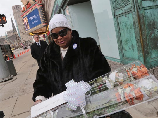 Lennette Williams, of Grosse Pointe Farms holds flowers she brought while representing the Rosa Parks Institute outside of the Fox Theatre in downtown Detroit after attending public memorial and visitation for the late Mike Ilitch on Wed., February 15, 2017.