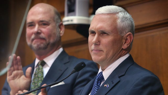 Speaker of the House Brian Bosma, R-Indianapolis (left) applauds Indiana Gov. Mike Pence, following Pence's third State of the State Address in the House chamber at the Indiana Statehouse on Jan. 13, 2015.