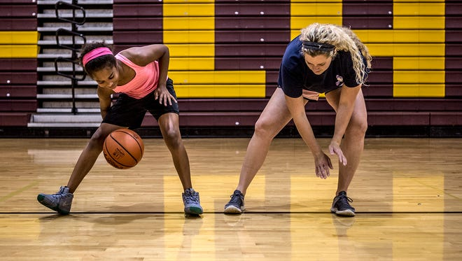 Licking Heights' JV coach, Lindsey Guth helps Kendyl Hunt, 10, with skills drills during a basketball camp.